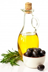 Bottle of olive oil and black olives.
